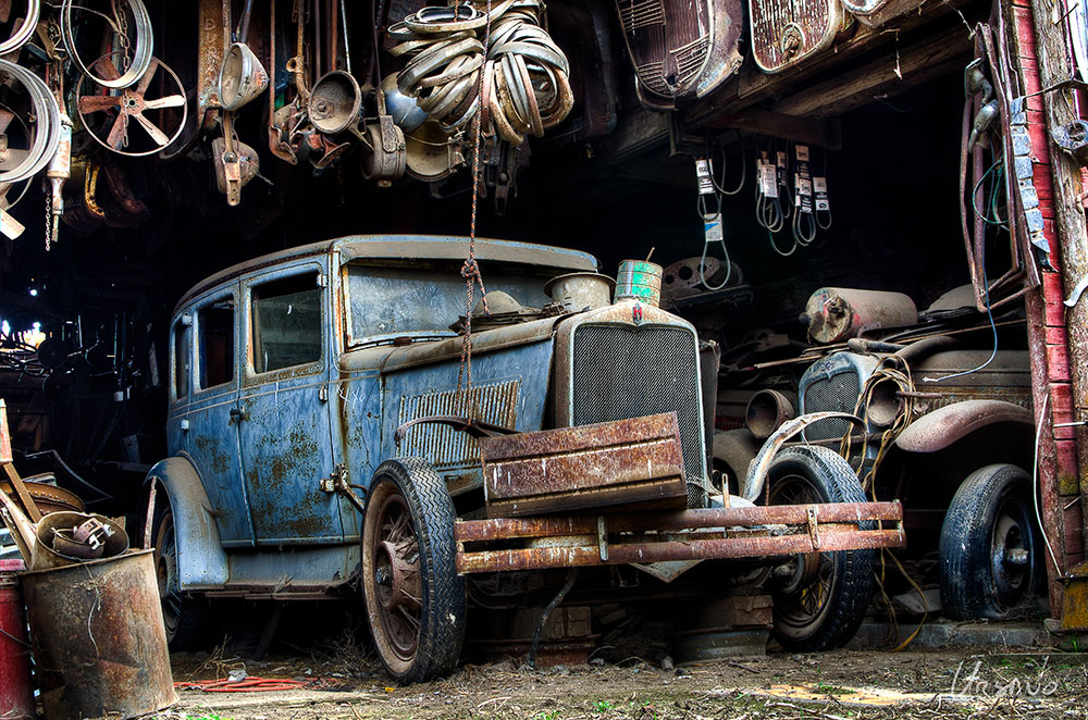 """""""Hupmobile #449"""" - Sitting in a garage as if it had just been pulled in for routine maintenance this late 1920's (1929?) Hupmobile sedan was one of the few in this junk yard that still had some color. Surrounded by car parts and flanked by an old Chevrolet sedan, this scene speaks to the role of cars in American history... and our fondness for working on them. This photograph of the old Hupmobile sedan is available as a limited edition metal print only."""